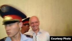 "В зал суда приводят Владимира Козлова, лидера незарегистрированной партии ""Алга"". Актау, 16 августа 2012 года. Фото с сайта Twitter."