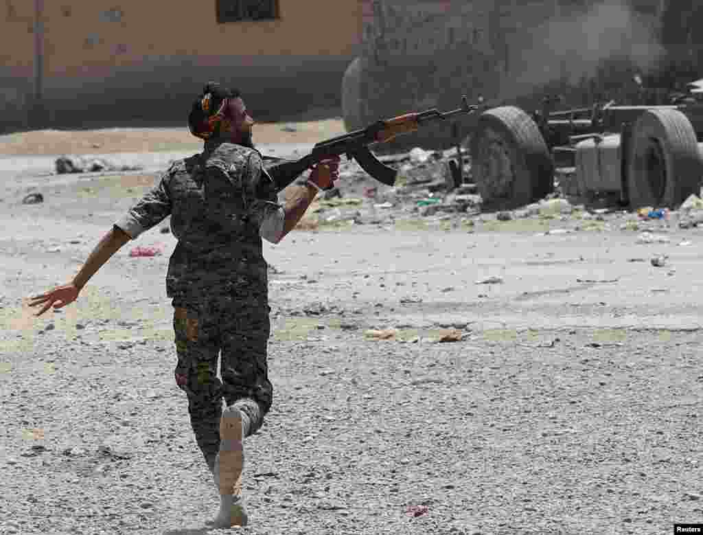A Syrian Kurdish fighter from the People's Protection Units (YPG) fires his rifle at Islamic State militants as he runs across a street in Raqqa on July 3. (Reuters/Goran Tomasevic)