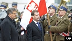 Russian President Dmitry Medvedev (center) and Polish President Bronislaw Komorowski inspect an honor guard during a welcoming ceremony in Warsaw.