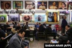 شهروندان عراقی در قهوهخانه ام کلثوم که مزین به تصاویری از او و دیگری هنرمندان عرب است