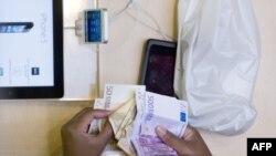 Клиент отсчитывает деньги на покупку нового iPhone в магазине Apple Store в Париже. 21 сентября 2012 года.