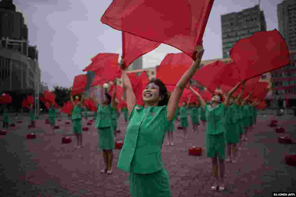 A propaganda troupe performs a flag-waving routine outside the central railway station in Pyongyang, North Korea. (AFP/Ed Jones)