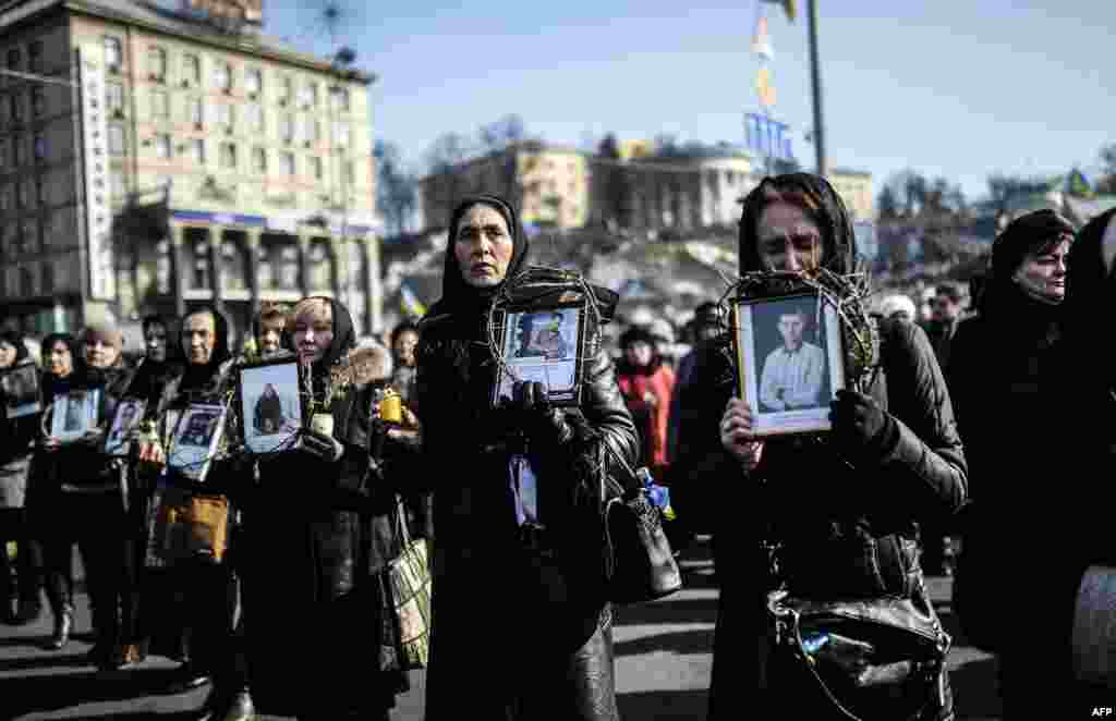 Women hold pictures of protesters who were killed in clashes with police during recent demonstrations as they take part in a commemerative procession in central Kyiv on February 26. (AFP/Bulent Kilic)