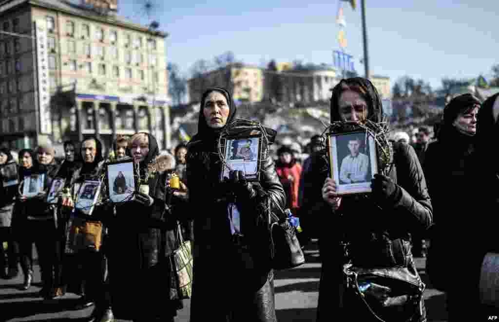 آن دسته از مردمی که عضوی از خانواده را در جریان درگیری ها در اوکراین از دست داده اند، با در دست گرفتن عکس آن ها، یادشان را گرامی می دارند