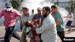 Сторонники свергнутого президента Мухаммеда Мурси уносят раненного с места столкновений. Каир, 5 июля 2013 года.