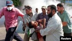 هواداران مرسی یکی از زخمیشدگان را از محل درگیری با ارتش، در برابر مقر گارد ریاست جمهوری، دور میکنند