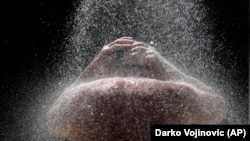SERBIA -- A man takes a cold shower in order to refresh herself at Ada Ciganlija lake in the Serbian capital, Belgrade, June 26, 2019