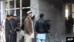 Afghans inspect the site of a bomb blast in Khost Province on January 6.