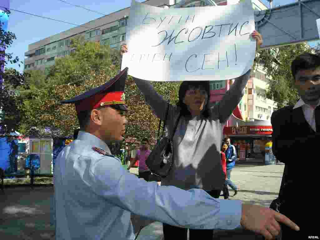 Полиция останавливает акцию поддержки Жовтиса. - Сторонница Жовтиса Ольга Уразбекова держит плакат с надписью «Сегодня Жовтис, завтра - Вы». Рядом стоит полицейский, который приказывает остановить акцию. Алматинский Арбат, 30 сентября 2009 года.