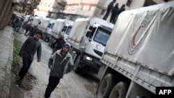 A Red Crescent convoy carrying humanitarian aid arrives in Kafr Batna, in the rebel-held Eastern Ghouta area, on the outskirts of the capital, Damascus, on February 23.