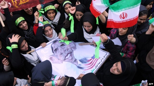 Iranian women hold an anti-U.S. sign, bearing a cartoon of U.S. President Barack Obama, outside the former U.S. Embassy in Tehran on November 2.