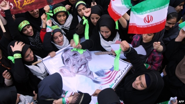 Iranian women hold an anti-American poster bearing a cartoon of U.S. President Barack Obama outside the former U.S. Embassy in Tehran on November 2.
