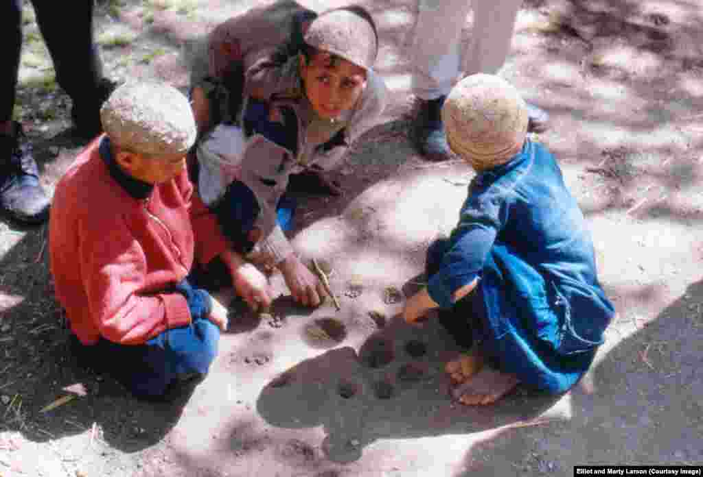 Local boys using sheep dung to play a game similar to mancala.