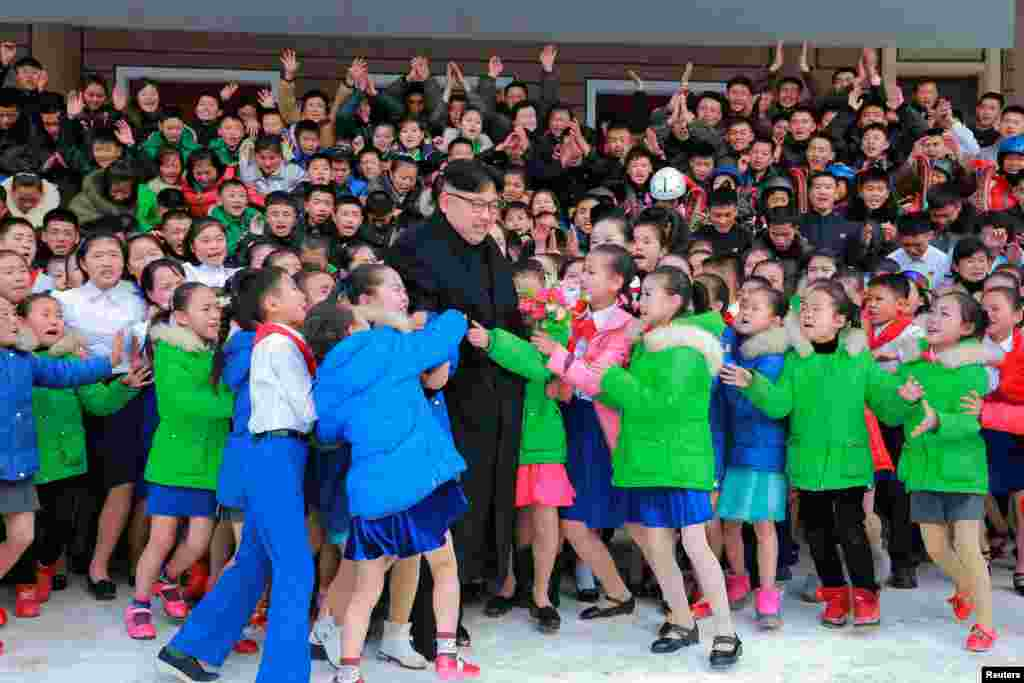 North Korean leader Kim Jong Un is hugged by children during a visit to Samjiyon County in this undated photo released by the Korean Central News Agency. (Reuters/KCNA)
