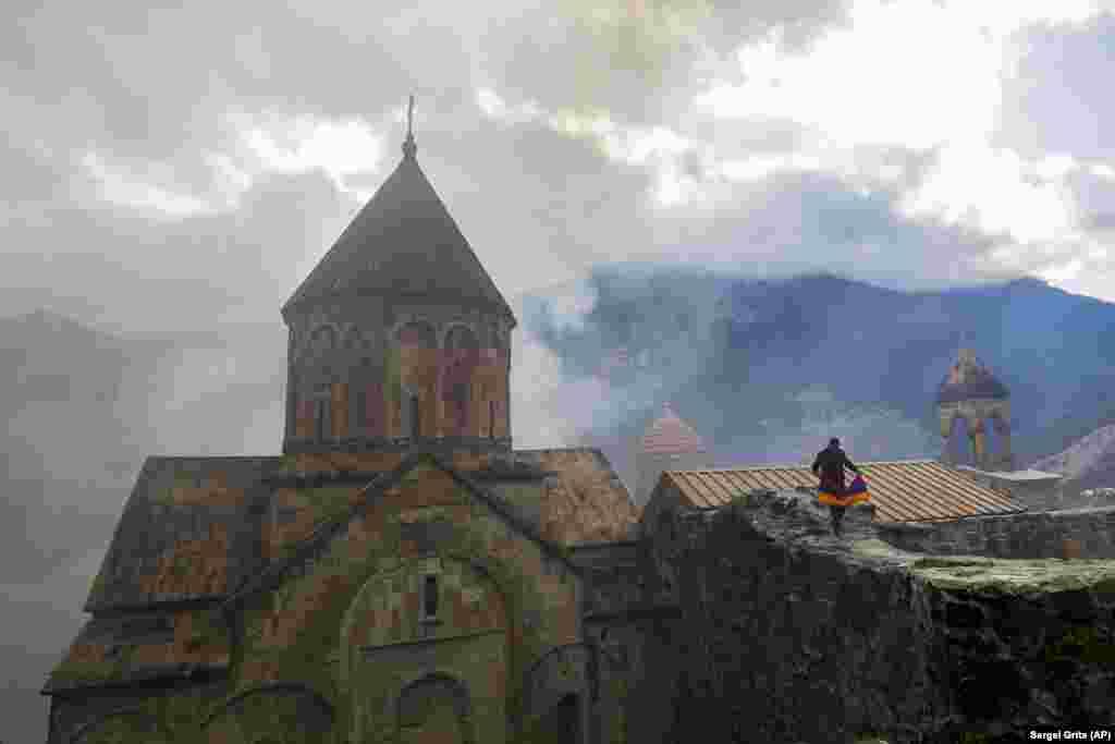 Ermenistannıñ milily bayrığı ili bir adam, Dağlıq Qarabağdaki Kelbercaranıñ kenarındaki XII-XIII asırlarğa ait olğan Dadivank keşişhanesini ziyaret ete, 2020 senesi noyabrniñ 13.