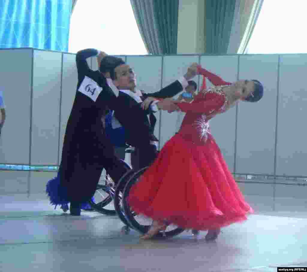 Молодой человек в инвалидной коляске танцует вальс на соревнованиях по танцам.