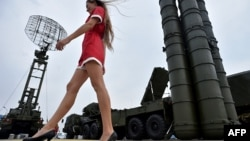 A woman walks past S-400 air-defense systems at a military exhibition outside Moscow.