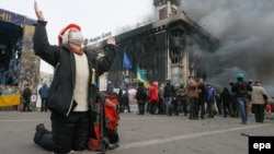 Украина -- Антиөкмөттүк демонстрацияга катышып жаткан бир аял Жаратканга жалбарып жатат. Киев, 19-февраль, 2014.