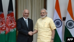 Afghan President Ashraf Ghani (left) and Indian Prime Minister Narendra Modi shake hands prior to a meeting in New Delhi on September 14.