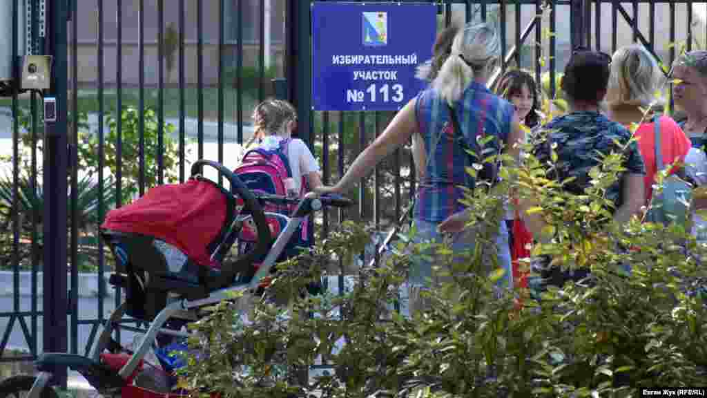 В школах Севастополя развернуты избирательные участки. Родители ожидают учеников младших классов у забора, так как свободный доступ на территорию городских школ закрыт из-за требований антитеррористической безопасности