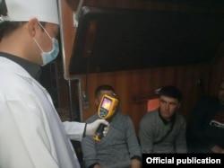 Өзбекстанда пойыз вагонындағы жолаушылардың дене қызуын тексеріп тұрған адам.