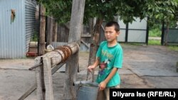 Младший сын Кожамуратовых у колодца во дворе.