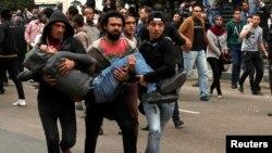 Եգիպտոս - Ցուցարարները տեղափոխում են բախումների ժամանակ վիրավորված երիտասարդին, Կահիրե, 25-ը հունվարի, 2015թ․