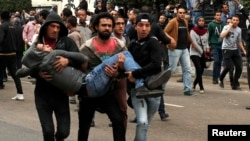 Антиурядові демонстранти допомагають пораненому учаснику протестів, Каїр, 25 січня 2015 року