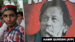 A supporter stands next to a poster of Pakistani cricketer-turned-politician Imran Khan.