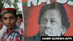 PAKISTAN - A supporters of Pakistan's cricketer-turned politician and head of the Pakistan Tehreek-e-Insaf (Movement for Justice) party Imran Khan stands next to poster with a picture of Khan as they gather near his residence in Islamabad on July 26, 2018