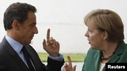 "German Chancellor Angela Merkel (right) welcomes France's President Nicolas Sarkozy before talks in Berlin on July 20, where the two are said to have agreed a ""common position"" on the eurozone's debt crisis."