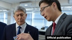 Дастан Догоев демонстрирует президенту Алмазбеку Атамбаеву ID-карту нового образца.
