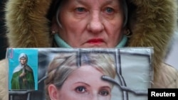A supporter holds a portrait of jailed opposition leader Yulia Tymoshenko during a rally in Kyiv in February 2013.