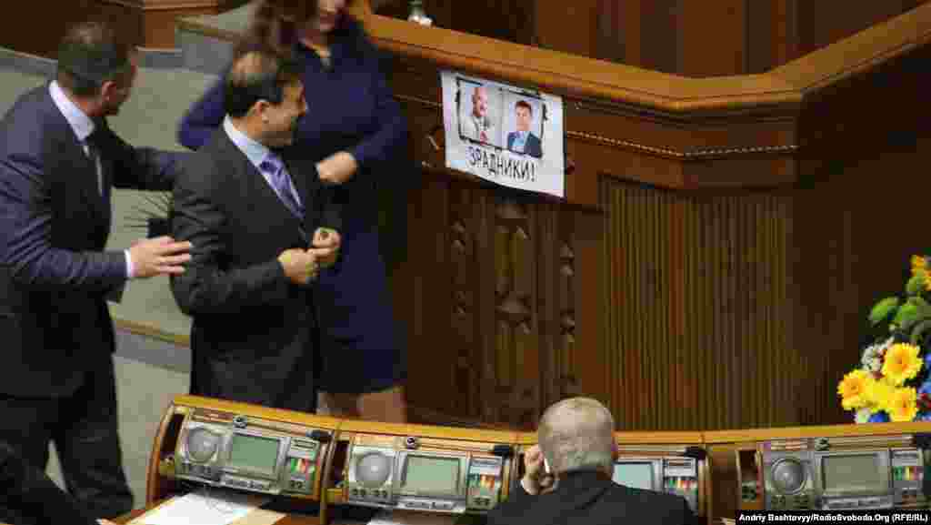 The inaugural session even came with its own fight card taped to the rostrum, in this case accusing father-and-son opposition lawmakers Andriy and Oleksandr Tabalov of planning to defect to the ranks of the ruling Party of Regions. Both Tabalovs were pushed from the chamber before they could be administered the parliamentary oath.