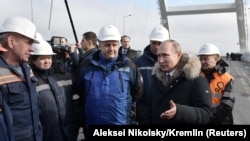 Russian President Vladimir Putin (second right) inspects a completed section of a bridge over the Kerch Strait that is meant to link Crimea to Russia.