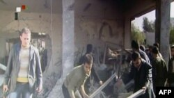 A screengrab from Syrian state TV shows people searching through rubble at the site of an apparent suicide attack at a security service base in Damascus.