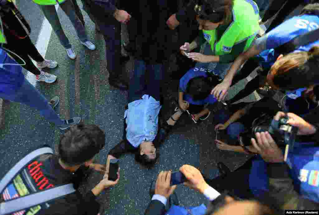 A woman lying on the ground after collapsing amid violent scuffles during the October 19 demonstration.