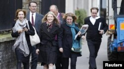 Ekaterina Zatuliveter (front, center) walks with lawyers to an immigration hearing in London in mid-October.