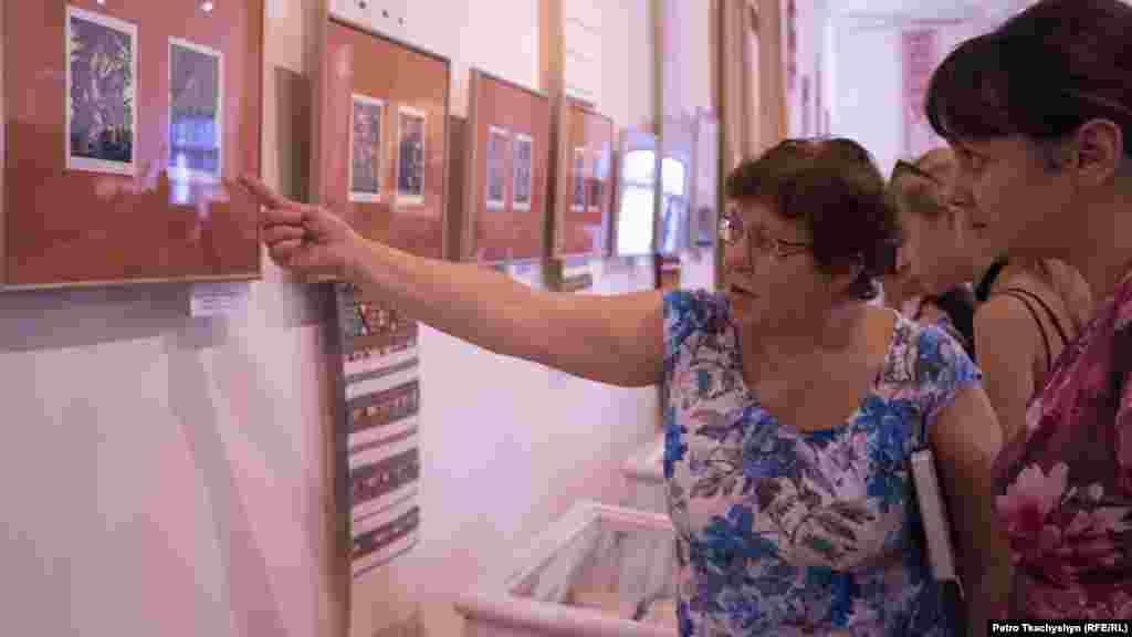 Працівниця музею показує відвідувачам рідкісні обкладинки до творів