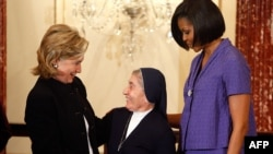 U.S. Secretary of State Hillary Clinton (left) presents the award to Sister Marie Claude Naddaf of Syria as first lady Michelle Obama looks on.