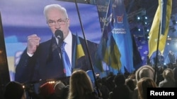 Supporters of the pro-presidential Party of Regions listen to Ukrainian Prime Minister Mykola Azarov speak as they attend a preelection rally in Kyiv on October 26.