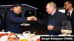 Қытай басшысы Си Цзиньпин (сол жақта) және Ресей президенті Владимир Путин Владивостоктағы кездесу кезінде стақан соғыстырып тұр. 11 қыркүйек 2018 жыл.