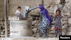 A young girl pumps water from a well in the village of Manugay in the Pech River Valley of Kunar Province, Afghanistan, in June.