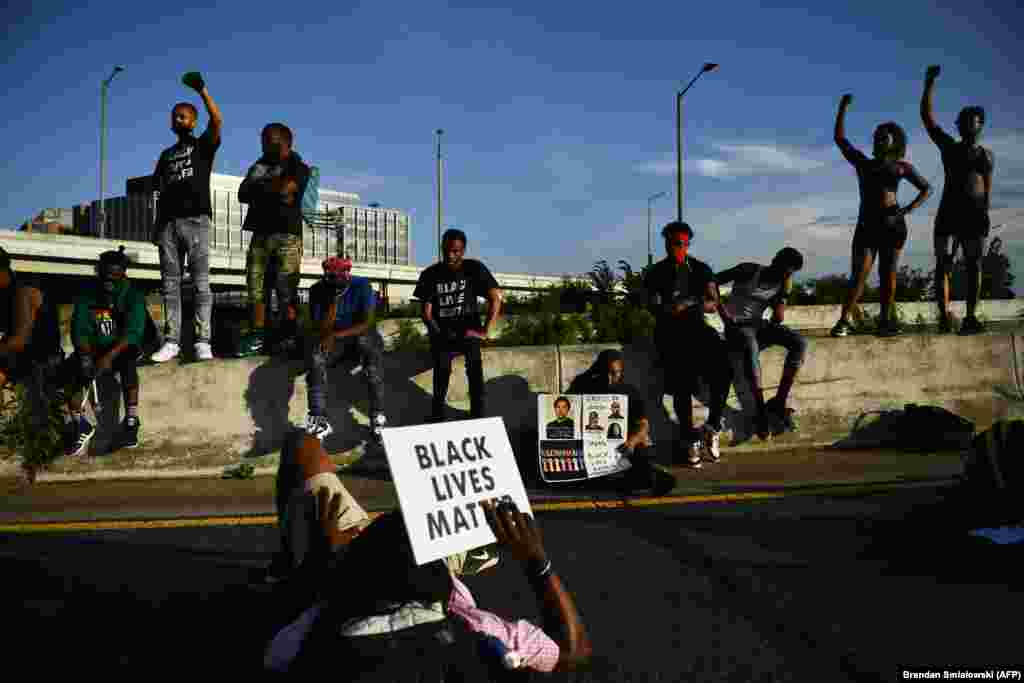 Demonstrators chant as others lay on a highway blocking traffic, as protests triggered by the death of George Floyd while in police custody, continue on June 23, 2020, in Washington, DC.