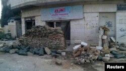اكياس من الرمل أمام أحد المحال في مدينة الحولة السورية