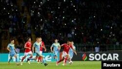 Казахстанские футболисты (в форме бирюзового цвета) в матче против сборной Дании.