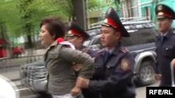 Полиция оппозициялық журналист Жанна Байтелованы ұстап әкетіп барады. Алматы, 1 мамыр 2010 жыл. (Көрнекі сурет)