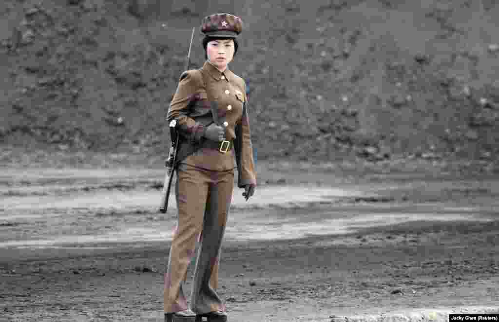 A female North Korean soldier stands guard along the banks of the Yalu River, near the town of Sinuiju, opposite the Chinese border city of Dandong. (Reuters/Jacky Chen)