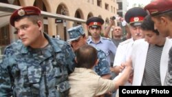 Tigran Arakelian is corraled by police in an undated photo from a protest in Yerevan