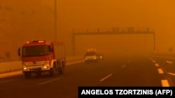 Пожарные машины в дыму пожаров в районе городка Кинета, Греция, 23 июля 2018 года.
